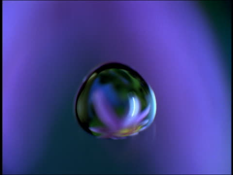 High speed close up tracking shot water drop falling with blue background