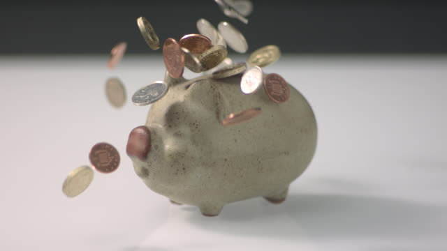 High speed Coins falling on and around piggy bank, none going in