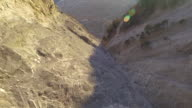 High speed drone flying along mountain cliff face, forest