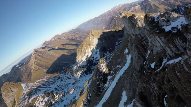 High speed drone flying along snowy mountain cliff face
