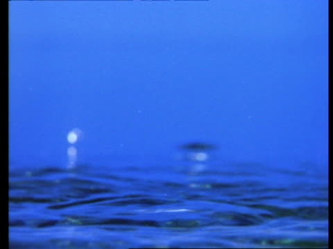 High Speed - Water drop falling, forming corona, blue background