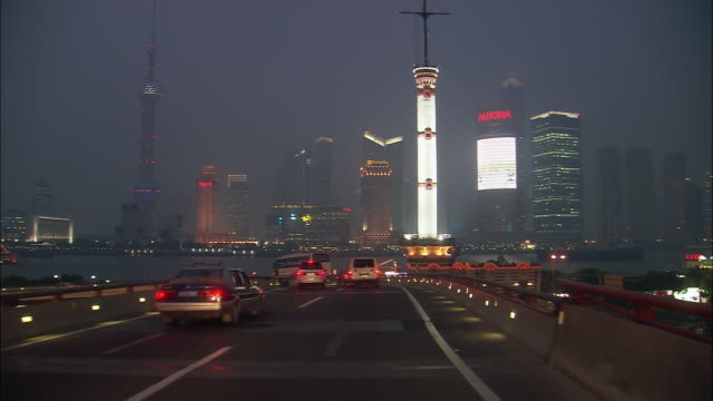 High speed wide shot driving point of view past Pudong skyline on freeway at night/ approaching the Bund/ Shanghai