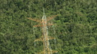 AERIAL High voltage electric transmission lines and steel support towers in rainforest / Cancun, Quintana Roo, Mexico