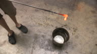 High-angle shot of a man creating a 'Prince Rupert's Drop' from molten glass, UK.