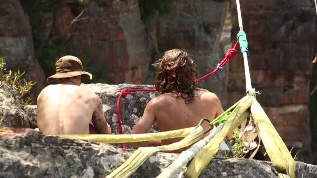 Highliners adjust their harnesses as they prepare to walk a highline rigged between cliffs at Corroboree Walls in Mount Victoria on March 8 2015 in...