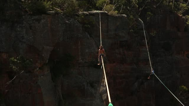 Highliners relax and focus on highlines rigged between cliffs at Corroboree Walls in Mount Victoria on March 8 2015 in the Blue Mountains Australia...