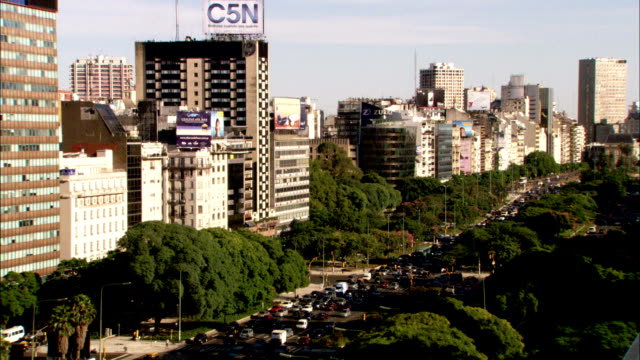 High-rise buildings tower over a busy street in Buenos Aires. Available in HD.