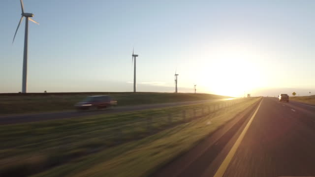 Highway driving passing wind turbine at Sunset