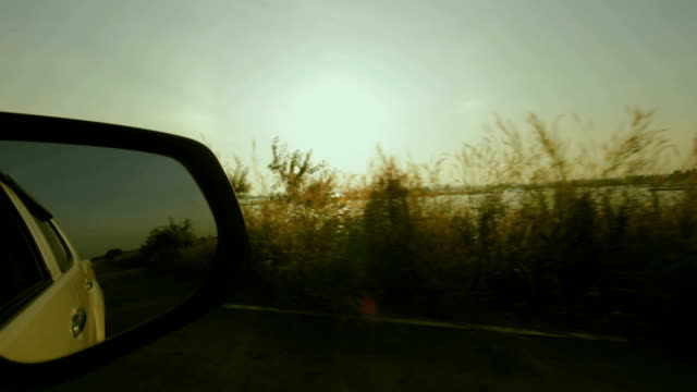 Highway travel seen from side mirror with a sunset