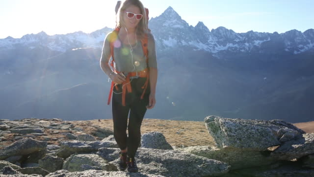 Hiker ascends mountain slope, to companion