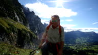 Hiker ascends path through mountain meadow
