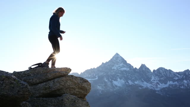 Hiker ascends to mountain summit, looks out to view