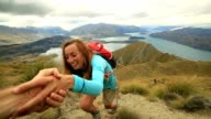 Hiker assists teammate on mountain top