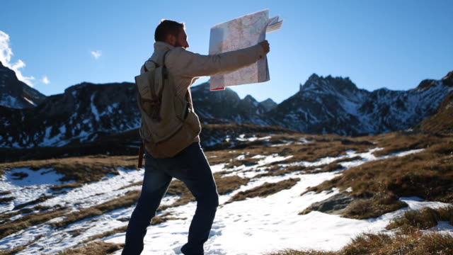 Hiker checks map at sunrise by mountain range