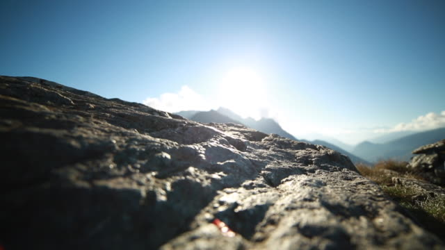 Hiker climbs along top of rock, arms outstretched