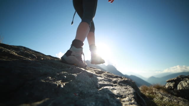 Hiker climbs along top of rock, outstretch arms