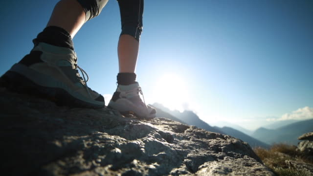 Hiker climbs along top of rock, outstretch harms