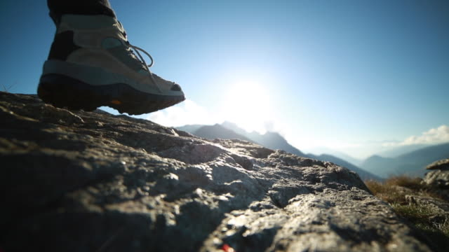 Hiker climbs along top of rock, outstretches arms