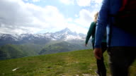 Hiker couple walk across mountain meadow