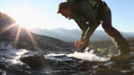 Hiker crosees creek, has drink, then continues up ridge