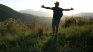Hiker crosses hillside, spreads arms wide