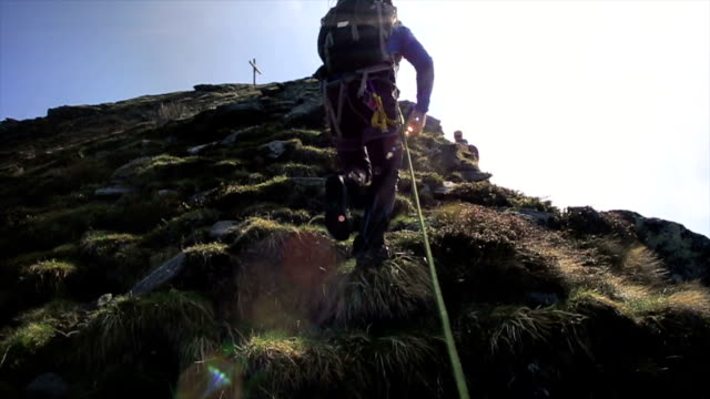 Hiker follows rope up steep slope towards cross, summit