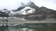 Hiker follows shoreline of lake below Matterhorn