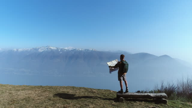Hiker looking at map from mountain top