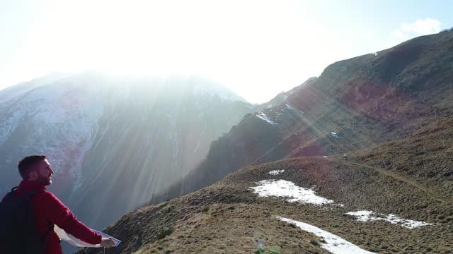 Hiker tittar på karta från bergets topp