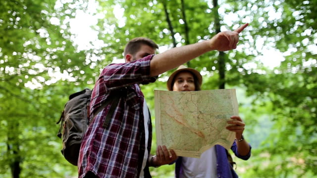 Hiker making a plan with a hiking map in forest