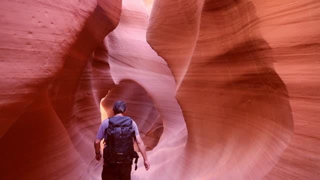 A hiker passes through a narrow passageway in Lower Antelope Slot Canyon, Page, Arizona.