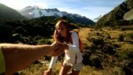 Wandelaar trekt hand om hulp te krijgen van teamgenoot