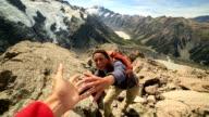Wandelaar trekt uit zijn hand om hulp te krijgen van teamgenoot