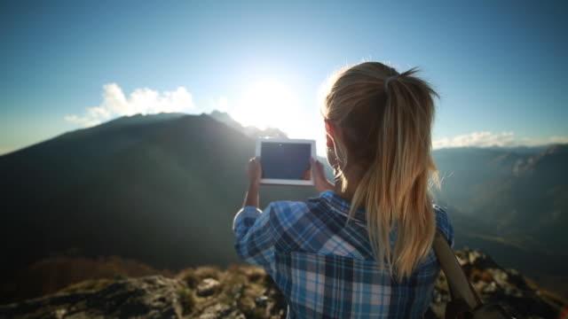 Hiker reaches mountain peak, takes picture