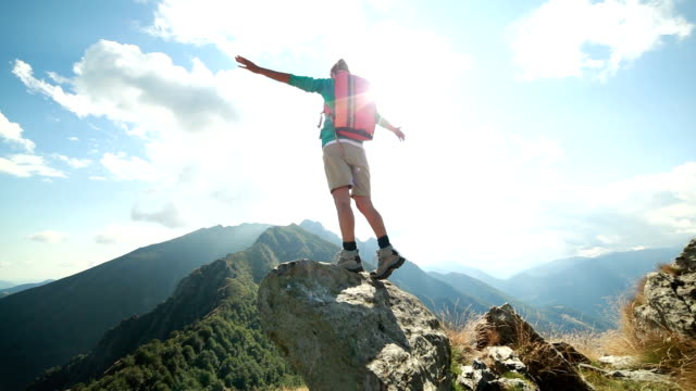 Hiker reaches mountain top, arms outstretched