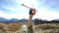 Wandelaar bereikt boven, uitgestrekte armen van de berg