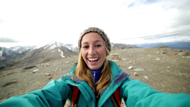 Wandelaar bergtop heeft bereikt, neemt 360 graden selfie