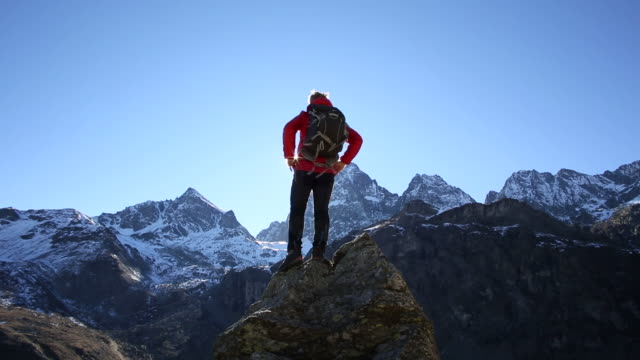 Hiker reaches pinnacle summit, spreads arms wide