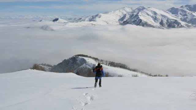 Hiker runs down snowy mountainside towards valley fog