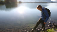 Hiker scoops clear water from mountain lake, drinks