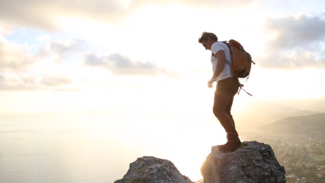 Hiker spans gap between rocks above sea, sunset