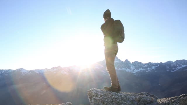 Hiker stands on mountain summit, looks out to view