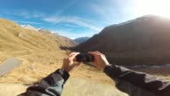 Hiker taking a video selfie with smartphone of 360 degrees view in the Italian Alps.