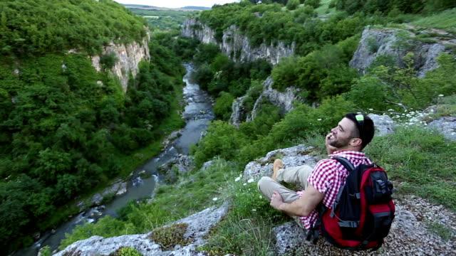 Wandelaar met behulp van slimme telefoon op de klif