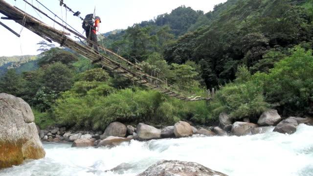 A hiker walks across a narrow, wooden foot bridge in the remote jungle of Myanmar