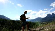 Hiker walks along mountain ridge above valley