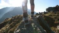 Hiker walks along narrow summit ridge crest