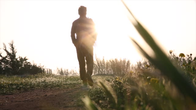 Hiker walks along rural track, looks out to sunrise