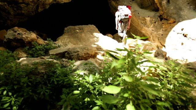 Hiker walks up path into cave entrance