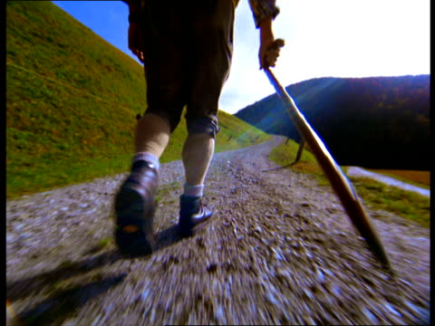 A hiker wearing knee-pants and carrying a stick walks along a dirt path in the mountains.